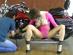 Tied slender beauty is posing on the bike